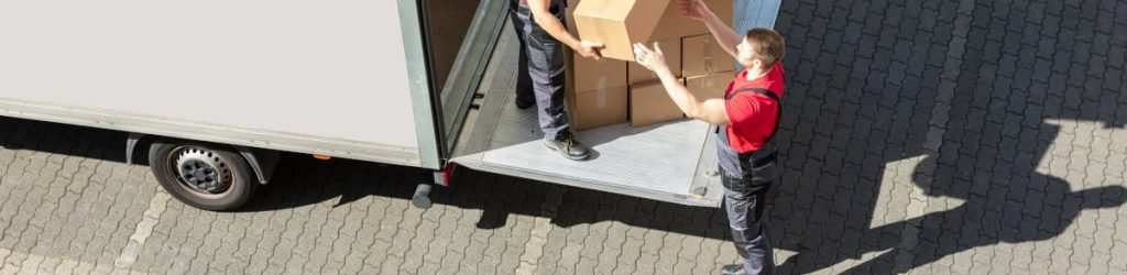 An Overhead View Of A Male Movers Unloading The Cardboard Boxes Form Truck On Street